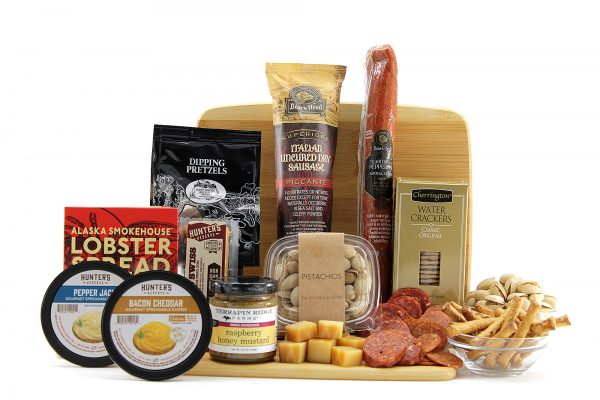 Assorted meats, cheeses, crackers, and more all displayed on a bamboo cutting board.