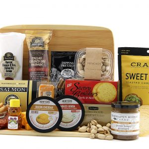 Assorted cheeses, crackers, meats, and more displayed on a bamboo cutting board.