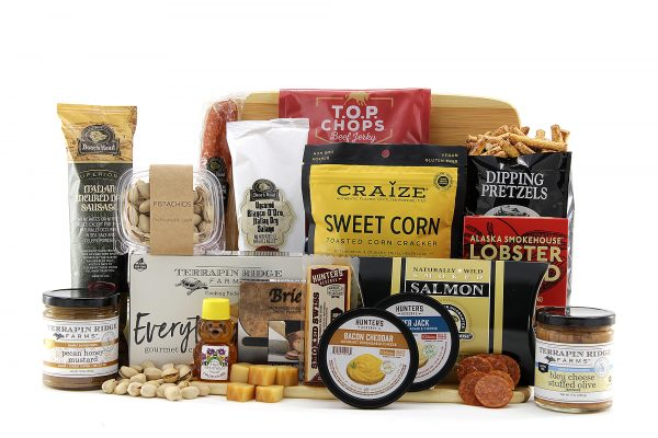 Generous portion of cheeses, meats, crackers, dips, and lots more all delivered on a bamboo cutting board.