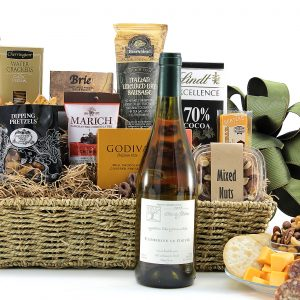 Gourmet gift basket with a variety of chocolate, meat, cheese, salty snacks, and a bottle of wine