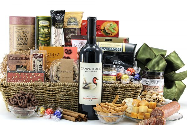 Generous gourmet gift basket filled with assorted chocolates, cheeses, salty snacks, bottle of wine, and more!