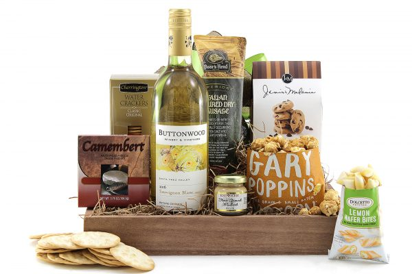 Gourmet gift basket with a variety of sweet and salty snacks and a bottle of wine.