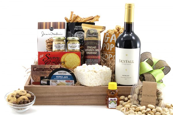 Gourmet gift basket with assorted sweet and salty snacks delivered with a bottle of wine.