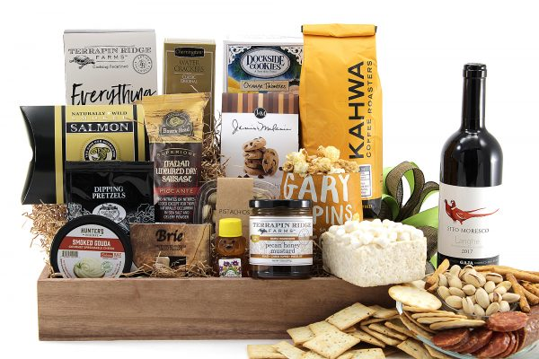 Huge assortment of gourmet treats including cheeses, meat, crackers, cookies, ground coffee, bottle of wine, and more!