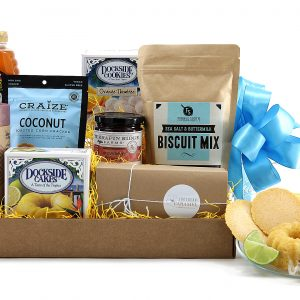 Gift basket designed with tea, honey, and snacks to match including key lime cake, orange thimble cookies, biscuit mix, and more.