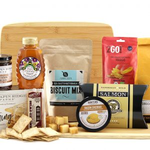 Assorted breakfast items including jam, smoked salmon, ground coffee, biscuit mix, and more all delivered on a bamboo cutting board.