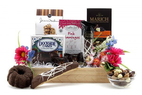 Gift Basket filled with assorted chocolatey treats and decorated with artificial flowers.