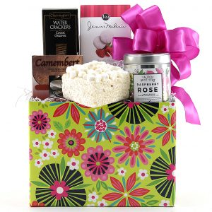Floral print gift basket filled with cheese, crackers, tea, and sweets.